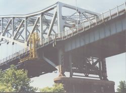 Suspended Work Platform Rolls Along Top of Exterior Sidewalk on an Overhead Truss Type Bridge